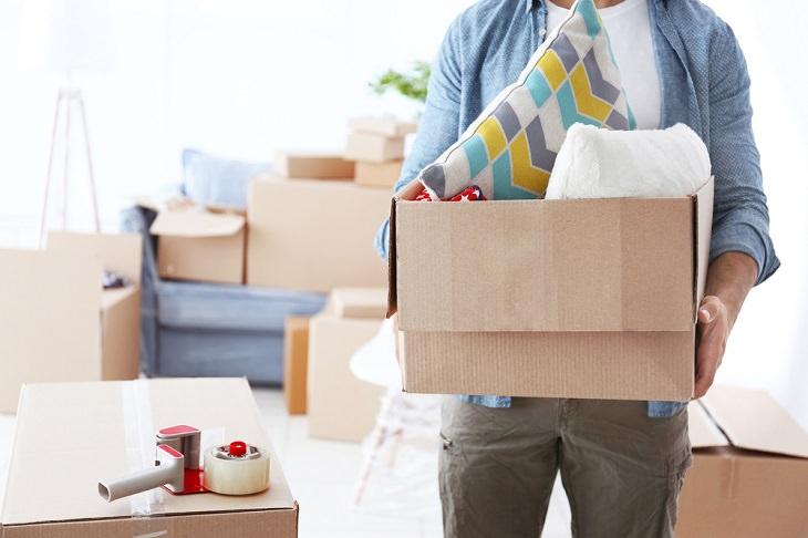 טיפים למעבר דירה: אדם סוחב קרטון עם חפציו בתוכו