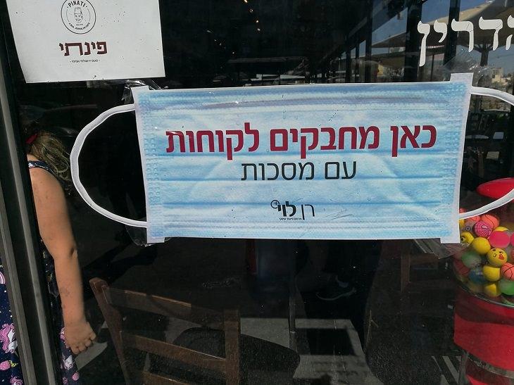 """שלטים מצחיקים: שלט על דלת עסק """"כאן מחבקים לקוחות םע מסכות"""""""