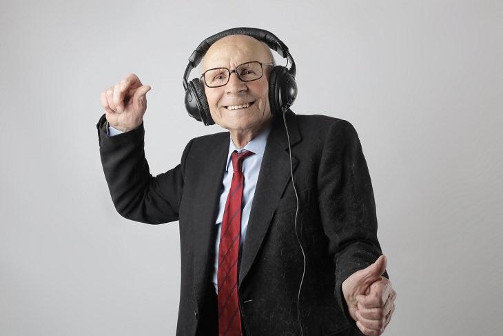 עונג מסוכן והנאות בריאות: איש מבוגר בחליפה שומע מוזיקה דרך אוזניות ורוקד