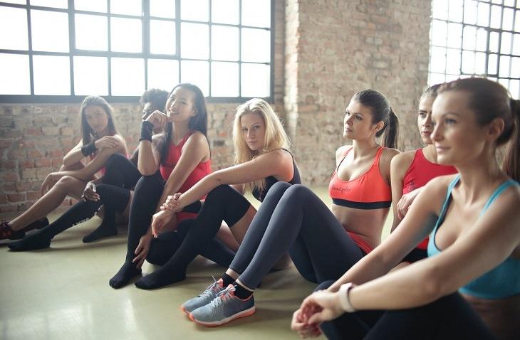 אימון בשיטת קלנטיקס: בחורות יושבות בסטודיו עם בגדי ספורט