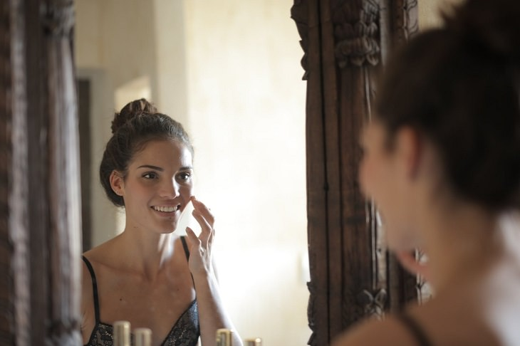 יתרונות בריאותיים של הדס: בחורה מחייכת ומסתכלת על עצמה במראה בעודה נוגעת בפנים שלה