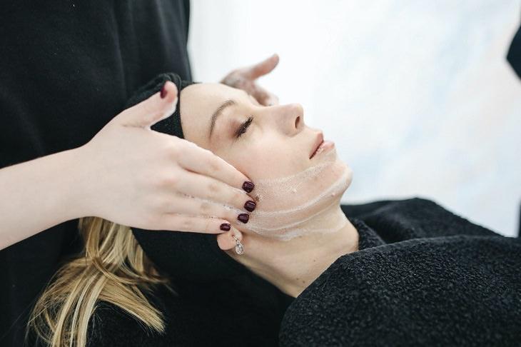 שיטות לטיפול בעור שומני: בחורה בטיפול פנים עם קרם