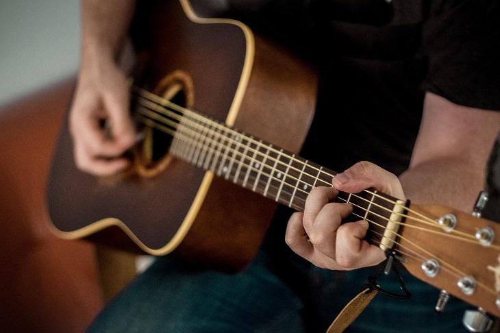מחקר על נגינה ושיעורי נגינה ראשונים: גבר מנגן על גיטרה