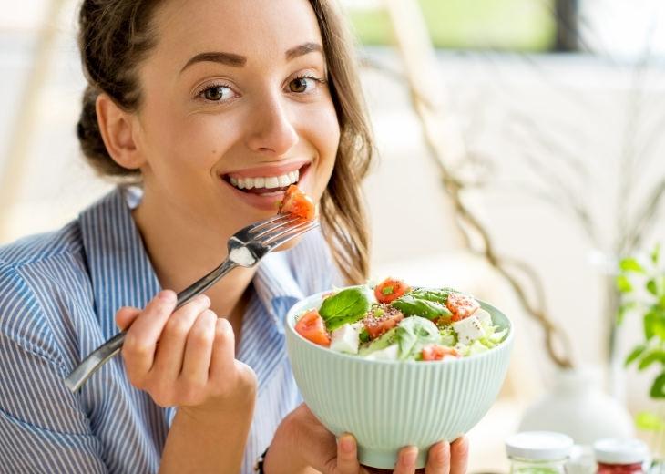 מניעת אכילת יתר בעבודה מהבית: אישה אוכלת סלט ומחייכת