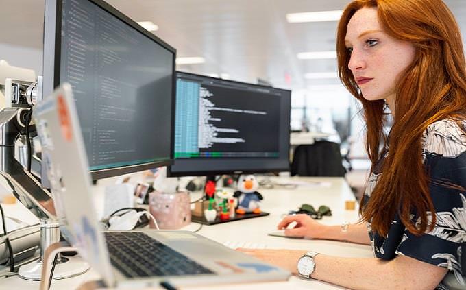 איזה אימוג'י אתה: בחורה יושבת בעמדה ומביטה על מסכי מחשב