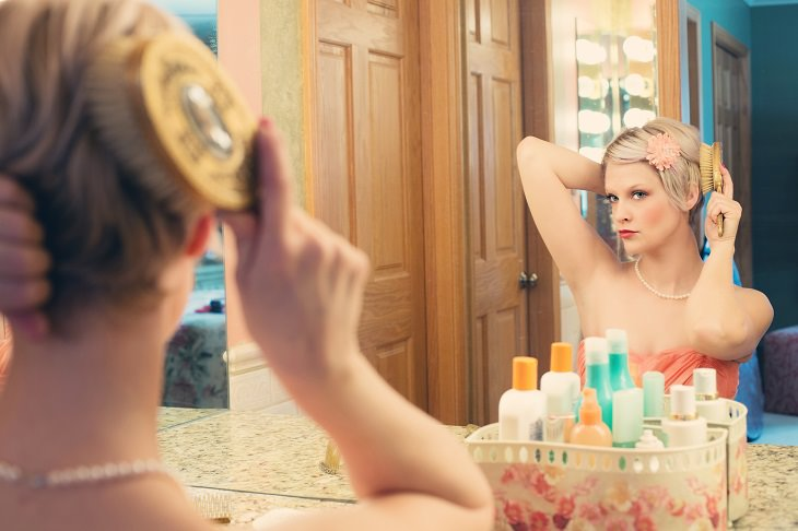 הרגלים שמגבירים קשקשת: אישה מסתרקת מול מראה