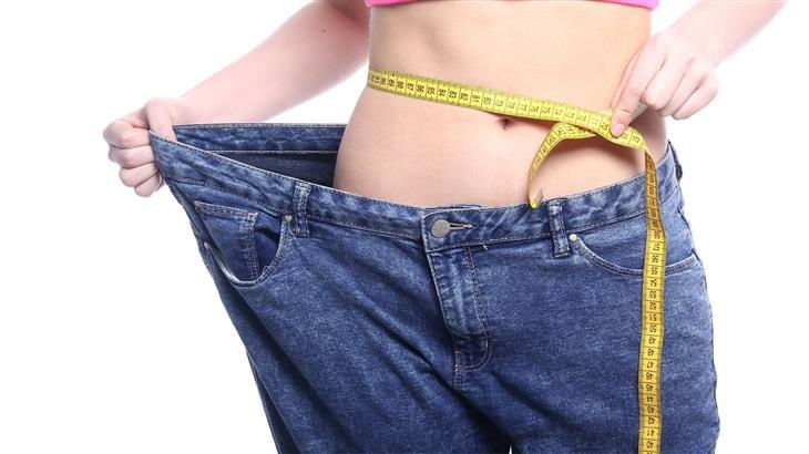 אנזים AMPK: אישה מודדת את מותניה ומציגה איך הג'ינס שלה כבר גדול עליה