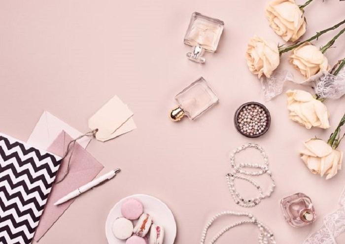 בשמים מומלצים: שולחן שעליו בשמים, פרחים, כלי כתיבה, תכשיטים ועוגיות