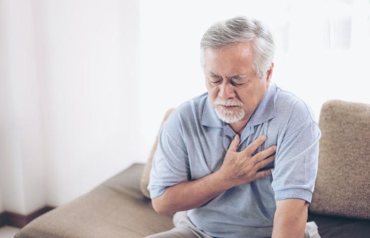 מיתוסים על כולסטרול: גבר תופס את חזהו בכאב
