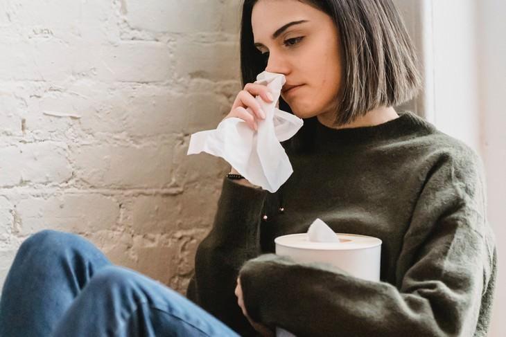 הגורמים לנזלת ודרכי הקלה: אישה מקנחת את האף