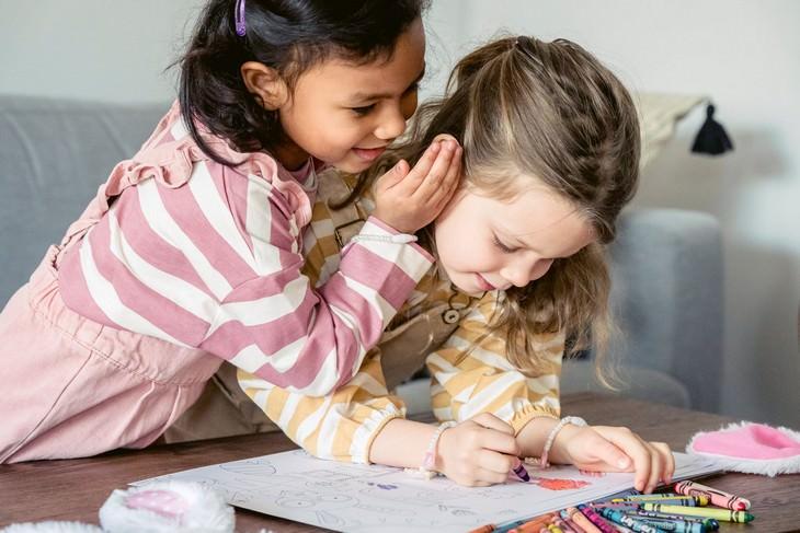 טריקים פסיכולוגיים להורים: ילדה לוחשת באוזן של ילדה אחרת