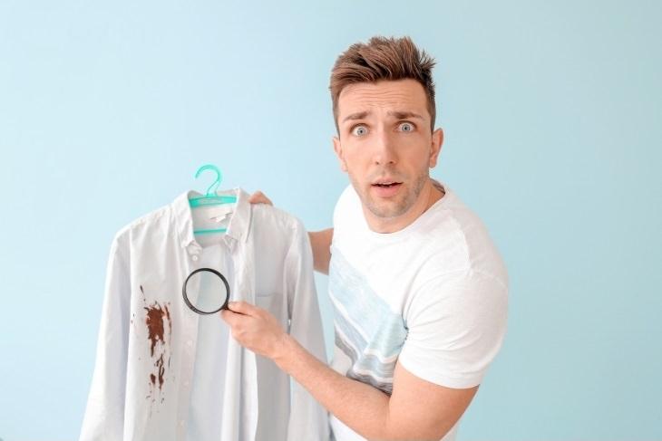 דרכים להסרת כתמי שוקולד: אדם מכוון זכוכית מגדלת לכתם שוקולד שעל חולצתו