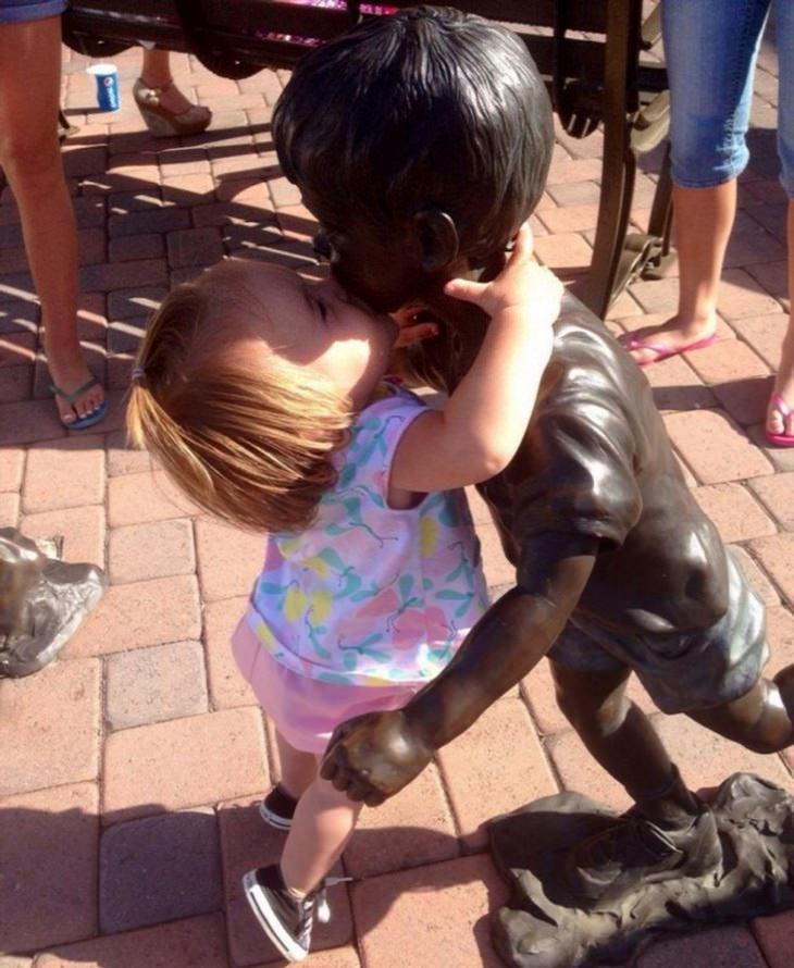 תמונות מחממות לב של ילדים מקסימים: ילדה מנשקת פסל על השפתיים