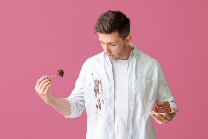 דרכים להסרת כתמי שוקולד: אדם מביט על החולצה שלו שהוכתמה מעוגת שוקולד