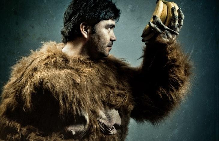 בדיחה על עובד גן חיות שהתחפש לגורילה: אדם בתחפושת גורילה מחזיק אשכול בננות