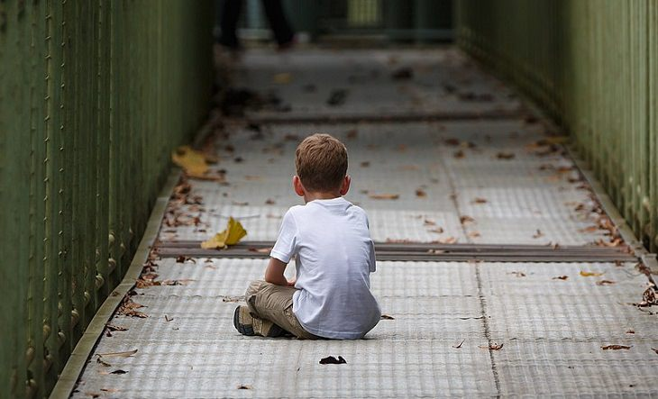 איך לא לגדל ילד עקשן: ילד יושב לבד על גשר