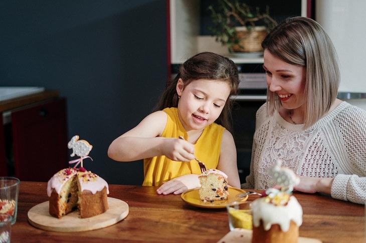 מחקר על תזונה לקויה בגיל צעיר: אימא יושבת ליד ילדה שאוכלת פרוסת עוגה