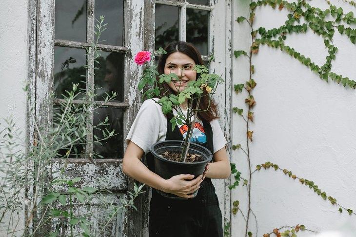 דרכים לגרום לילדים לאהוב גינון: נערה מחזיקה עציץ עם פרח