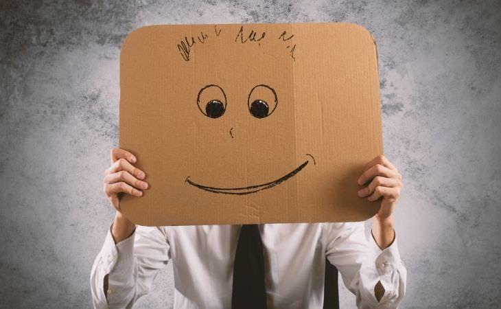 איך תקווה משפיעה על הבריאות וכיצד לאמץ אותה: איש מחזיק קרטון עם פרצוף מחייך מול פניו