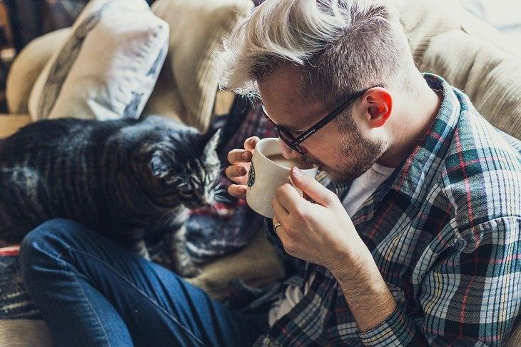 שיטות לגרום לחתול שלכם לאהוב אתכם יותר:  אדם שותה קפה והחתול שלו לצידו
