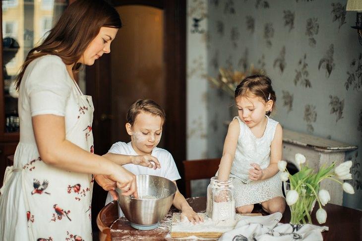 איך ללמד ילדים לבשל: אימא מערבבת והילדים שלה משחקים עם קמח