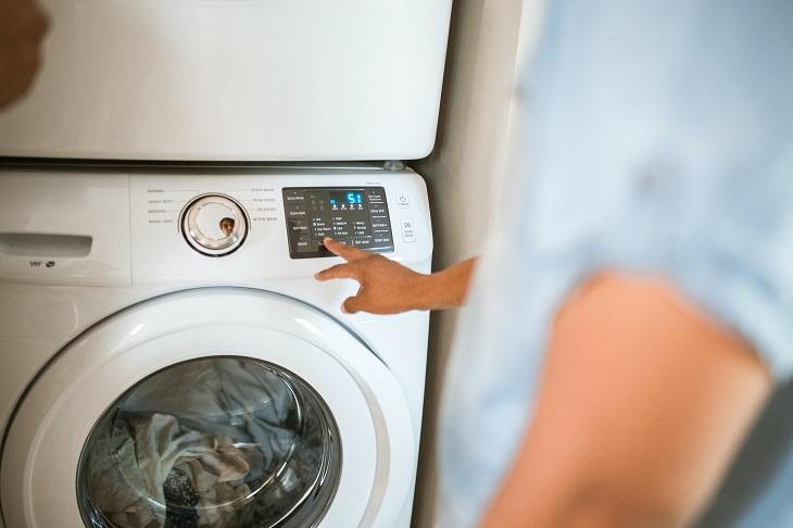 מטלות בית שאפשר לוותר עליהן: גבר מפעיל מכונת כביסה מלאה בבגדים