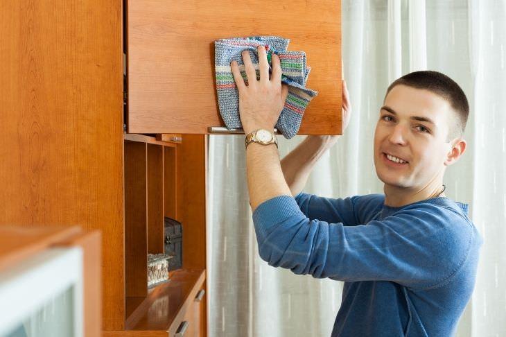 מטלות בית שאפשר לוותר עליהן: בחור מנקה ארון עץ עם מגבת