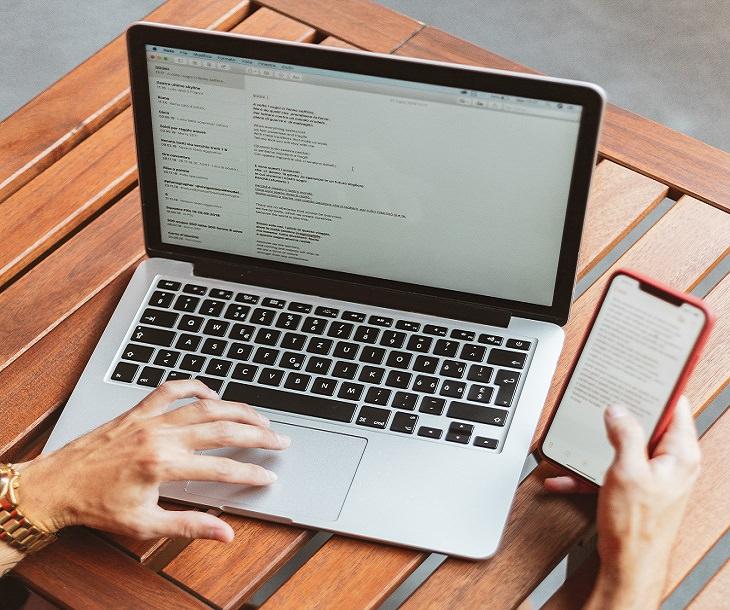 בחירת חברת פרסום: אדם עובד עם מחשב נייד וטלפון סלולרי