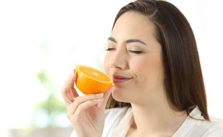 איך להחזיר את חוש הריח: אישה מריחה תפוז