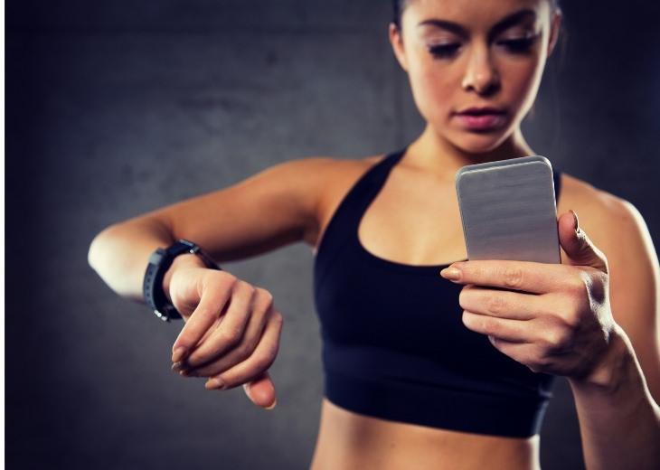 שעונים חכמים: אישה משתמשת בטלפון חכם ושעון חכם