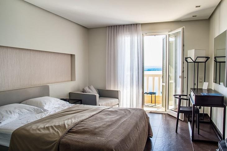 טעויות עיצוב בדירה קטנה: חדר שינה עם וילון בצבע הקיר שמגיע עד לרצפה
