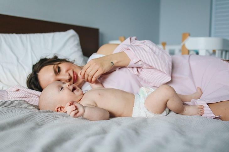 מחקרים על נוגדנים לקורונה בחלב אם: אימא שוכבת במיטה לצד תינוק