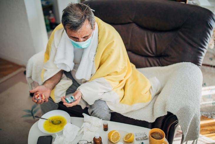 דברים שלמדנו על הקורונה:אדם עם מסיכה על פניו יושב על ספה עטוף שמיכות ומסביבו כדורים