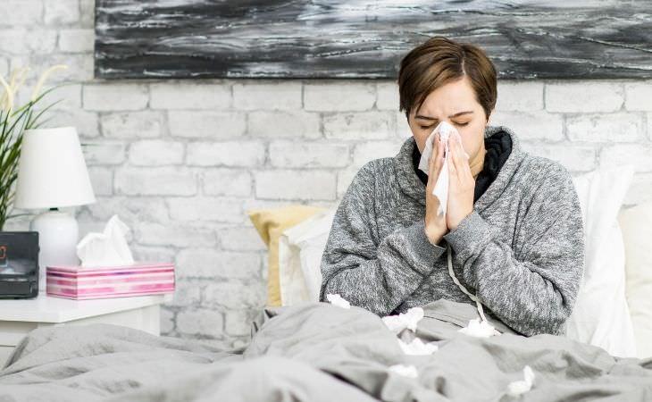 סקר על ימי מחלה בשנת הקורונה: אישה מקנחת את האף במיטה