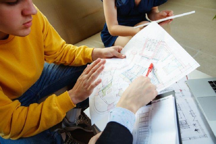 כיצד לתכנן שיפוץ בבית: אנשים יושבים על תוכנית מתאר של דירה ומתכננים שיפוץ