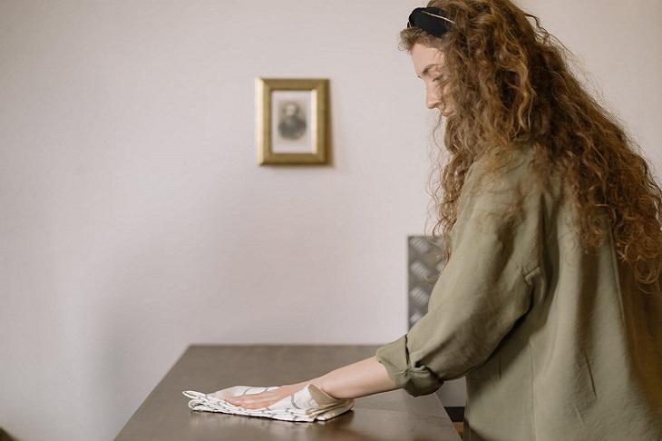 הרגלים שעלולים להזיק לציפורניים: אישה מנקה רהיט עם מגבת, ללא כפפות