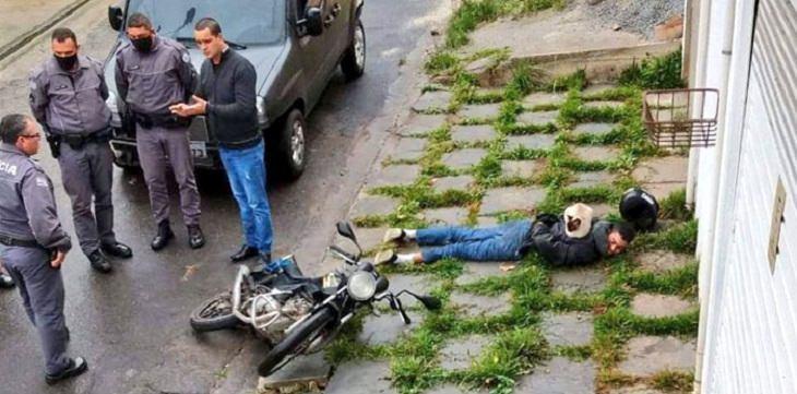 חתולים שיושבים במקומות מוזרים: חתול שוכב על בחור ששוכב על המדרכה כשידיו מאחורי גבו, ולידם חבורת גברים מדברים