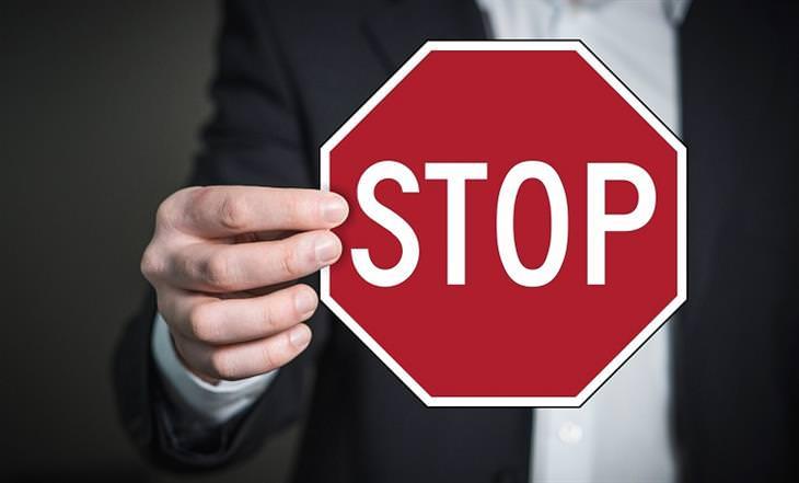אסטרטגיות להתמודדות עם לחץ בעבודה: גבר בחליפה מחזיק שלט עצור