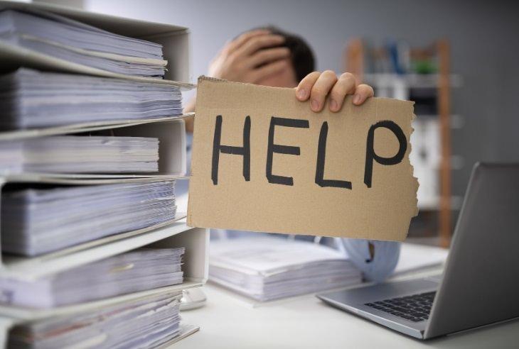 """בדיחה על בעל עסק שתלה שלטים במשרד: עובד במשרד מרים שלט מקרטון שעליו רשום """"עזרה"""""""