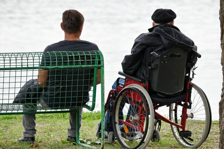 טעויות בתביעת ביטוח סיעודי: איש על ספסל ליד זקן בכיסא גלגלים