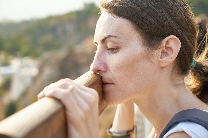 גזלייטינג: אישה מביטה במבט עצוב ורציני מעבר למעקה