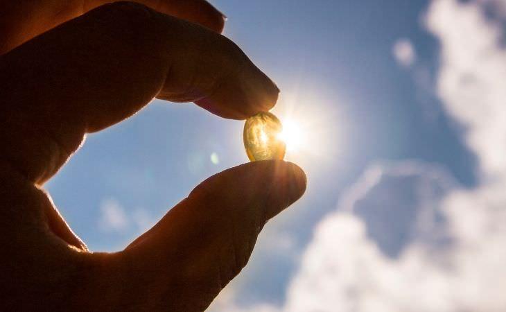 שילובי ויטמינים ומינרלים מומלצים ומסוכנים: יד מחזיקה טבליה של ויטמין D מול השמש