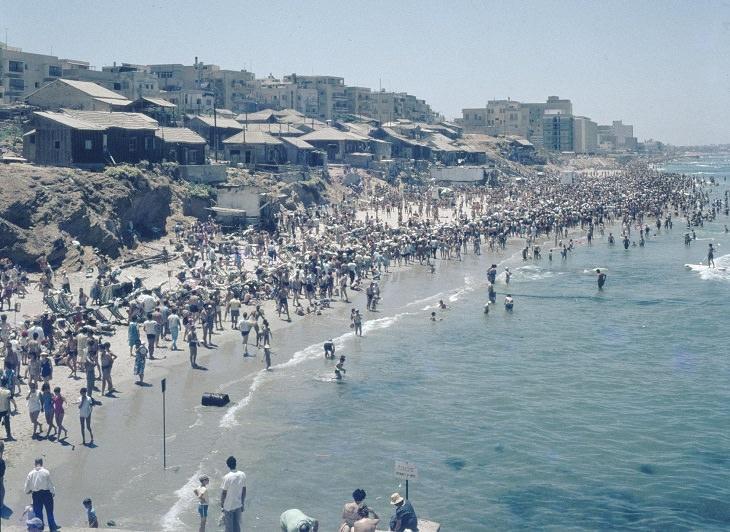 תמונות נוסטלגיות של תל אביב: אנשים מבלים בחוף גורדון, ברקע צריפי שכונת מחלול