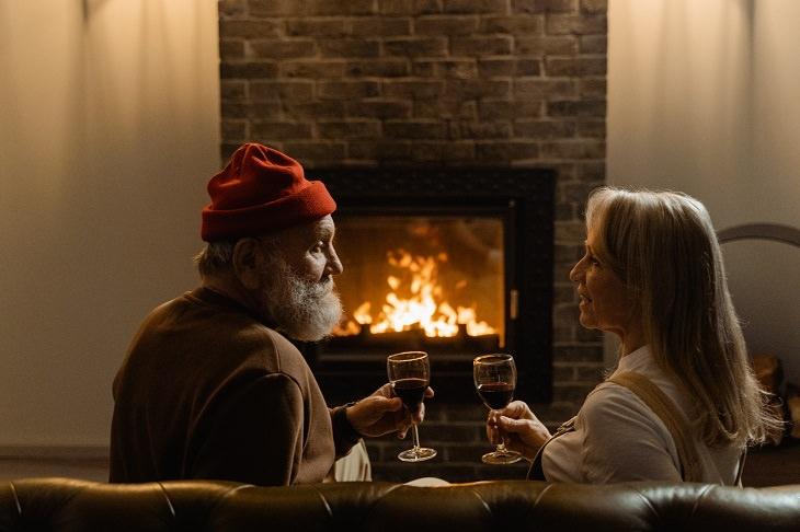 טיפים לריענון זוגיות משעממת: זוג מבוגר שותה יין מול אח