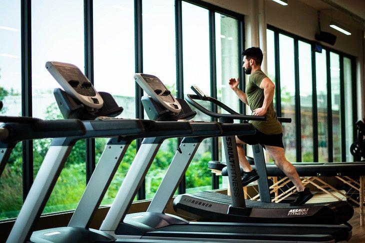 עלים ירוקים לחיזוק השרירים: גבר רץ על הליכון בחדר כושר