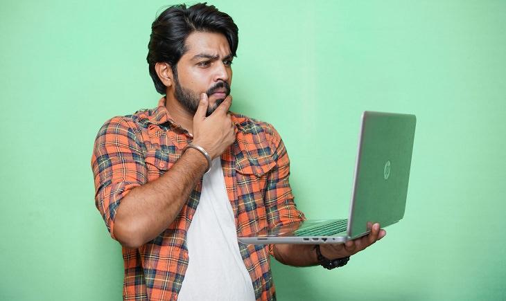 בדיחה: גבר מבולבל מחזיק מחשב נייד