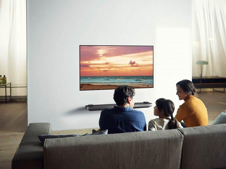 מדריך לקניית מסך טלוויזיה: משפחה יושבת מול מסך OLED