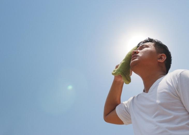 מחקר על קשר בין חום לבין דום לב: גבר עומד תחת השמש הקופחת ומנגב זיעה ממצחו