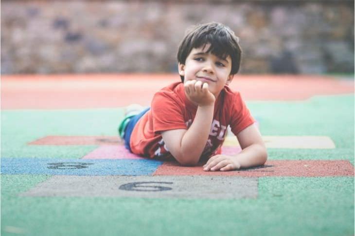 הספקטרום האוטיסטי: ילד שוכב על מדרכה בגינה וחולם