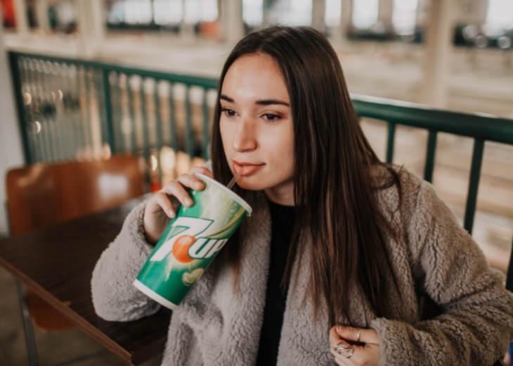 פעולות והרגלים שגורמים לכאבים בגב התחתון: אישה שותה משקה קל